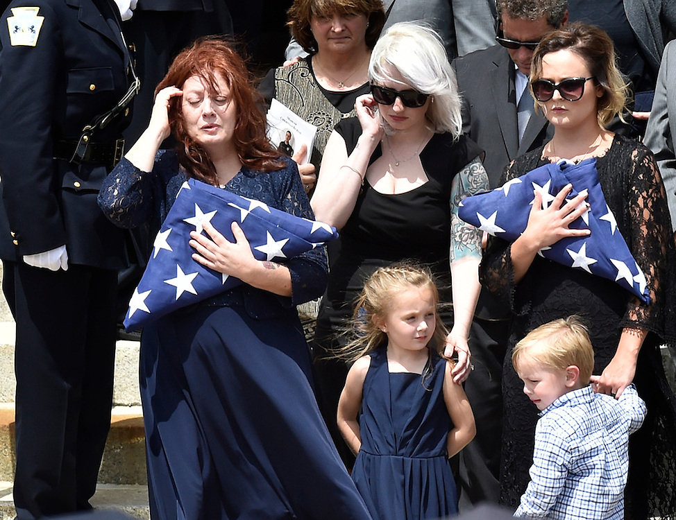 Officer John Wildings mother Mary,  and wife Kristen hold flags presented to them after the funeral for Wilding at St. Peter's Cathedral. Patrice Wilding (center) sister of Wilding holds his daughter Lola Mae and Kristen holds her son Sidney.  7/17/2015 Aimee Dilger Times Leader
