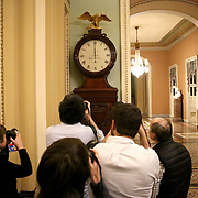 Photographers point their cameras towards the Ohio Clock outside the Senate Chamber at midnight as a lapse in government funding begins on Saturday, January 20, 2018.