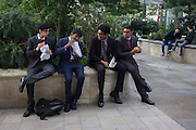 Four men of Asian appearance share a funny moment while eating lunch in a City of London park.