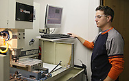 CNC Machinist Ben Goodin keeps an eye on a milling machine at Softronics LTD in Marion on Monday, February 11, 2013.
