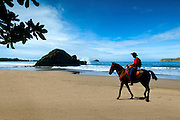 Local Costa Rican cowboy rides horseback over the beaches of Manuel Antonio.