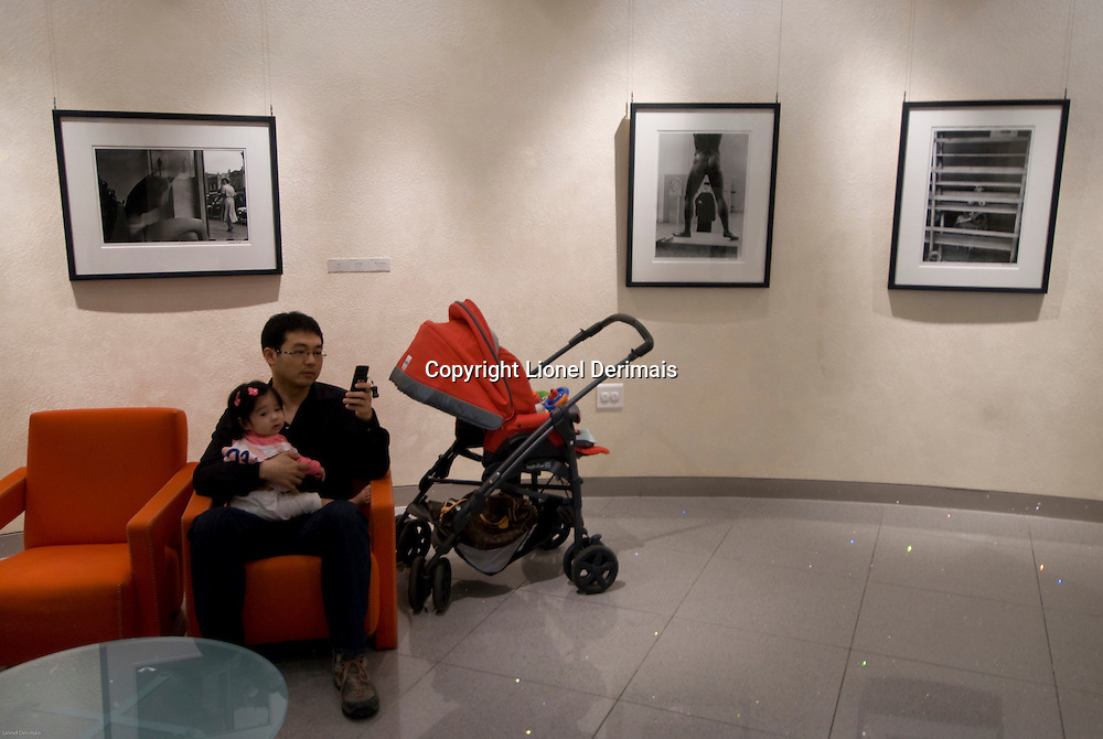 A  father and his daughter in the Shinsegae department store rest room's waiting room in Central Seoul, South Korea. 2009