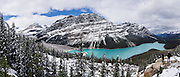 Snow covers the Waputik Range above turquoise Peyto Lake (1860 m or 6100 ft), in the Canadian Rockies, Banff National Park, Alberta. Bill Peyto was an early trail guide and trapper in the Banff area. Suspended rock particles of glacial rock flour create its bright  turquoise colour. Bow Pass (2068 m or 6787 ft) is the highest point on the Icefields Parkway, and a side road leads to a nature trail to Peyto Viewpoint (and higher bus road to wheelchair access). The lake is fed by Peyto Creek, which drains water from Caldron Lake and Peyto Glacier (part of the Wapta Icefield). Peyto Lake is the origin of the Mistaya River, which heads northwest. Banff National Park is Canada's oldest national park, established in 1885. Banff is part of the Canadian Rocky Mountain Parks World Heritage Site declared by UNESCO in 1984. This panorama was stitched from 7 overlapping images.