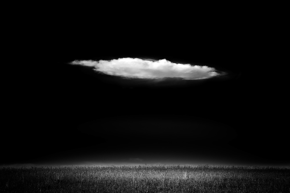 A lone cloud drifts over pastures near Cochrane Alberta
