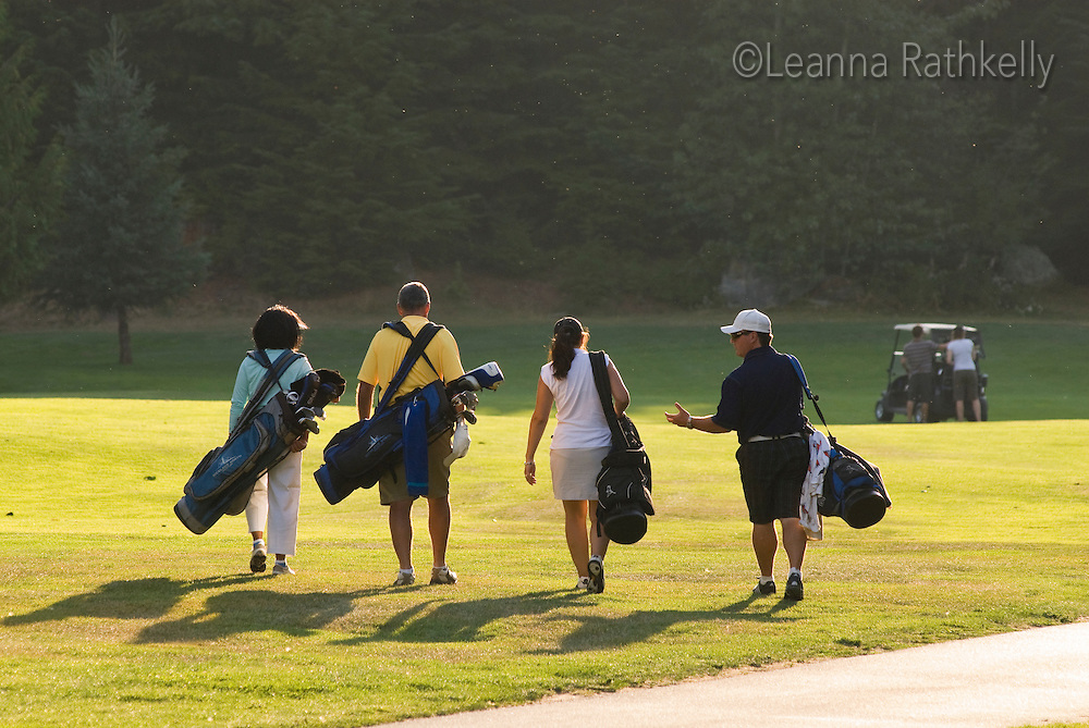 A foursome of golfers walks the Whistler course in the last light of a summer evening