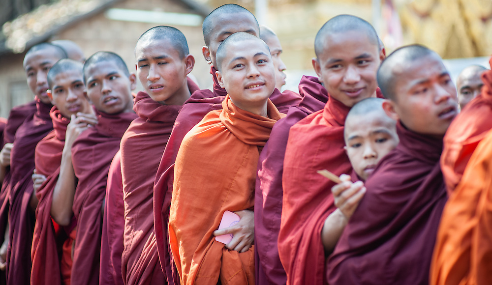Young Buddhist monks in line wrapped in their robes (Myanmar)