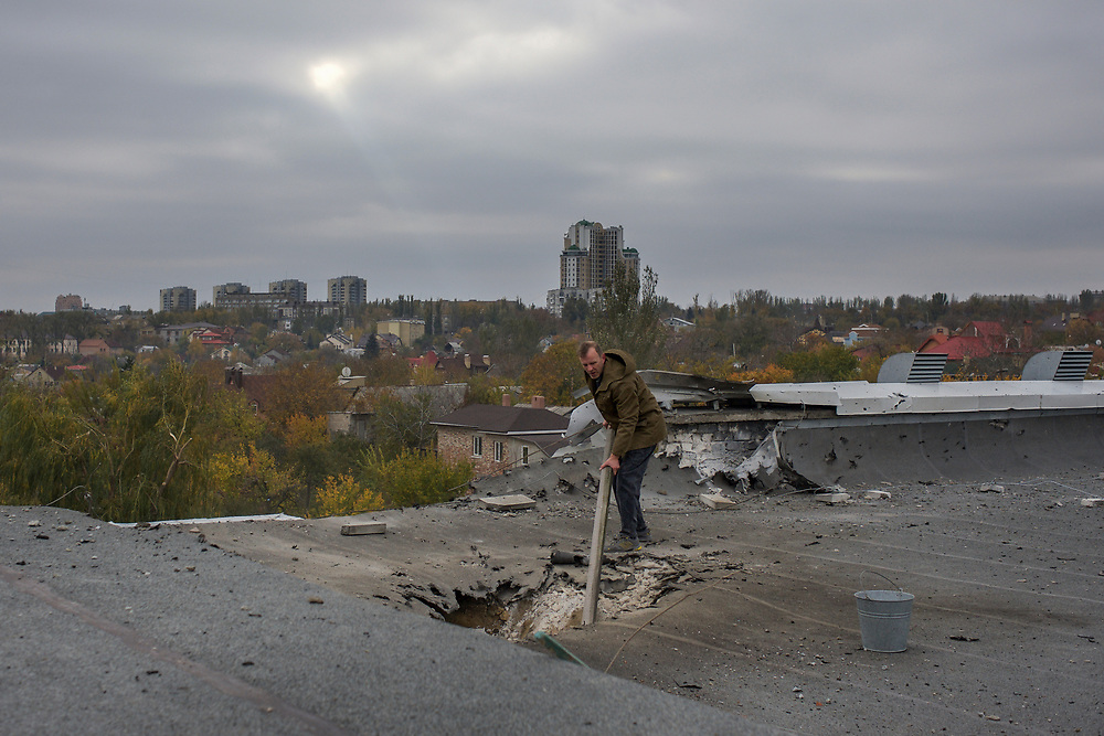 A volunteer worker checks the damaged to the roof of the gymnastic pavilion of School 61 in central Donetsk, hours after it was hit by shell presumably shot by the Ukrainian National Guard troops fighting for the control of the city's airport area.