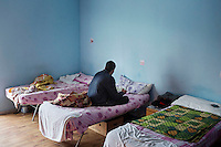 SALEMI, ITALY - 9 DECEMBER 2014: An asylum seekers from Pakistan read the Quran on his bed at the CAS (Special Accommodation Center) in Salemi, Italy, on December 9th 2014.<br /> <br /> The CAS (Special Accommodation Center) in Salemi, Sicily, hosts a total of 77 migrants from Nigeria, Mali, Togo Senegal, Gambia, Bangladesh, Camerou, Egypt, Ivory Coast, Burkina Faso and Pakistan.