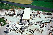 Nederland, Leiderdorp, Bospolder, 17/05/2002; bouwterrein ('site') HSL boortunnel onder het Groene Hart, Noordelijke toerit en startschacht; haaks op de schacht - met witt dak - de overkapping van waaruit de tunnel elementen naar de tunnelboormachine gehesen worden; onder in beeld de (eigen) betonfabriek' infrastructuur, bouwen, spoor, rail, TGV planologie ruimtelijke ordening, bouwplaats, kraan;<br /> luchtfoto (toeslag), aerial photo (additional fee)<br /> foto /photo Siebe Swart