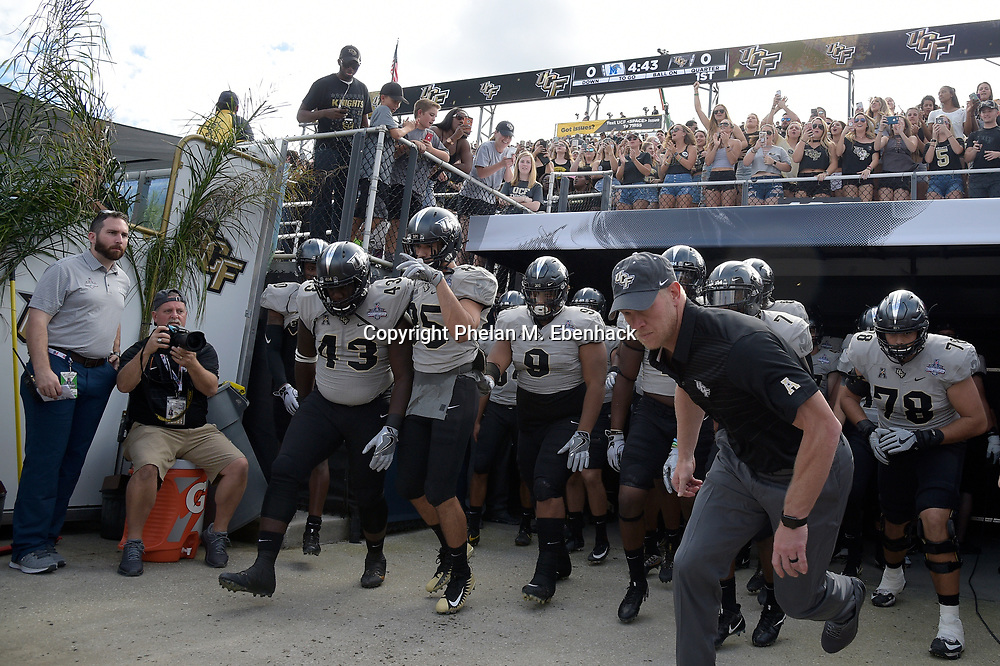 Central Florida head coach Scott Frost, right, leads the team onto the field before the American Athletic Conference championship NCAA college football game against Memphis Saturday, Dec. 2, 2017, in Orlando, Fla. (Photo by Phelan M. Ebenhack)
