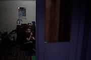 Arbi Khancoshvili (16) watches TV at home.  Duisi, Republic of Georgia.