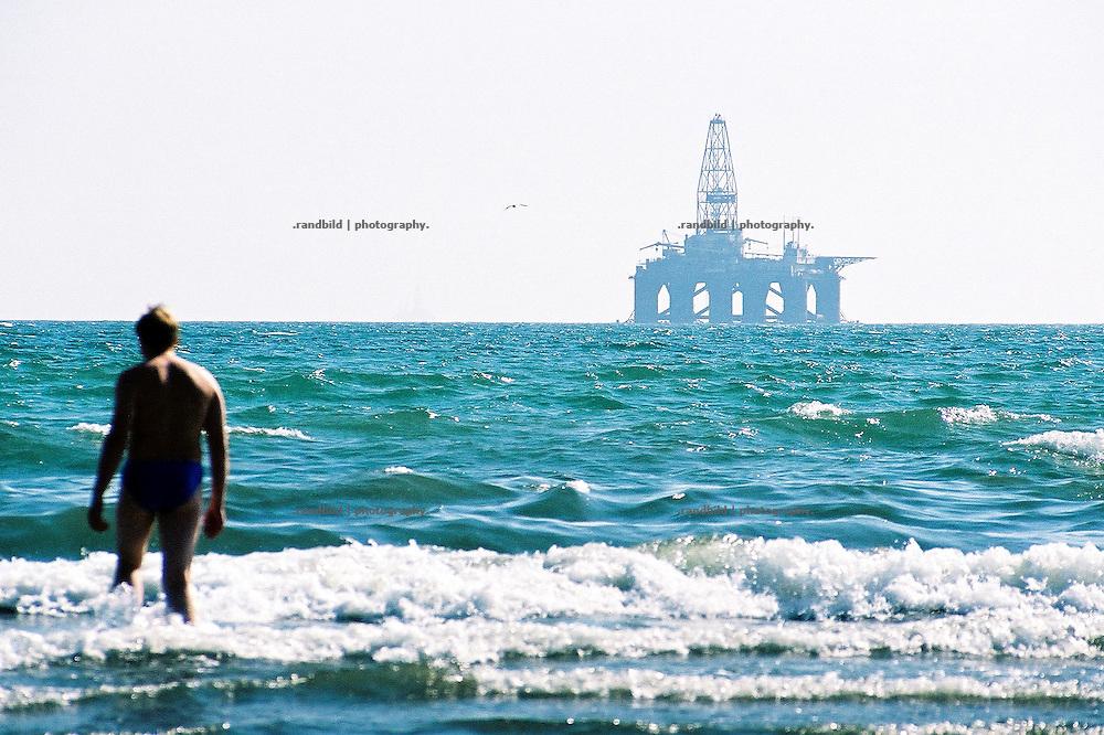 Während die Rohölpreise immer weiter steigen, nutzen südlich der aserbaidschanischen Hauptstadt Baku Touristen die letzten warmen Tage des Jahres für ein erfrischendes Bad im Kaspischen Meers. Die großen westlichen Ölkonzerne haben unlängst ihre Förderplattformen im Meer aufgestellt, um die riesigen Erdölvorkommen der Kaspischen Region für den europäischen und US-Markt auszubeuten. Die frühere Sowjetrepublik Aserbaidschan ist nicht Mitglied der OPEC und damit unabhängig in der Preisgestaltung. Die stählernen Ungetüme überrall in der See zeugen von diesem profitablem Geschäft für Ölfirmen und Regierung...Aseris and Tourists enjoy the Caspian Sea near Baku. Crude drill platforms are seen at the horizon.
