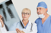 Senior male surgeon and female doctor looking at x-ray over gray background