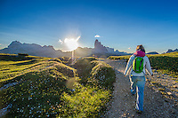 A back view of a female athlete as seen on a cold but sunny Summer morning, hiking on Monte Piana, South Tyrol, Italy.