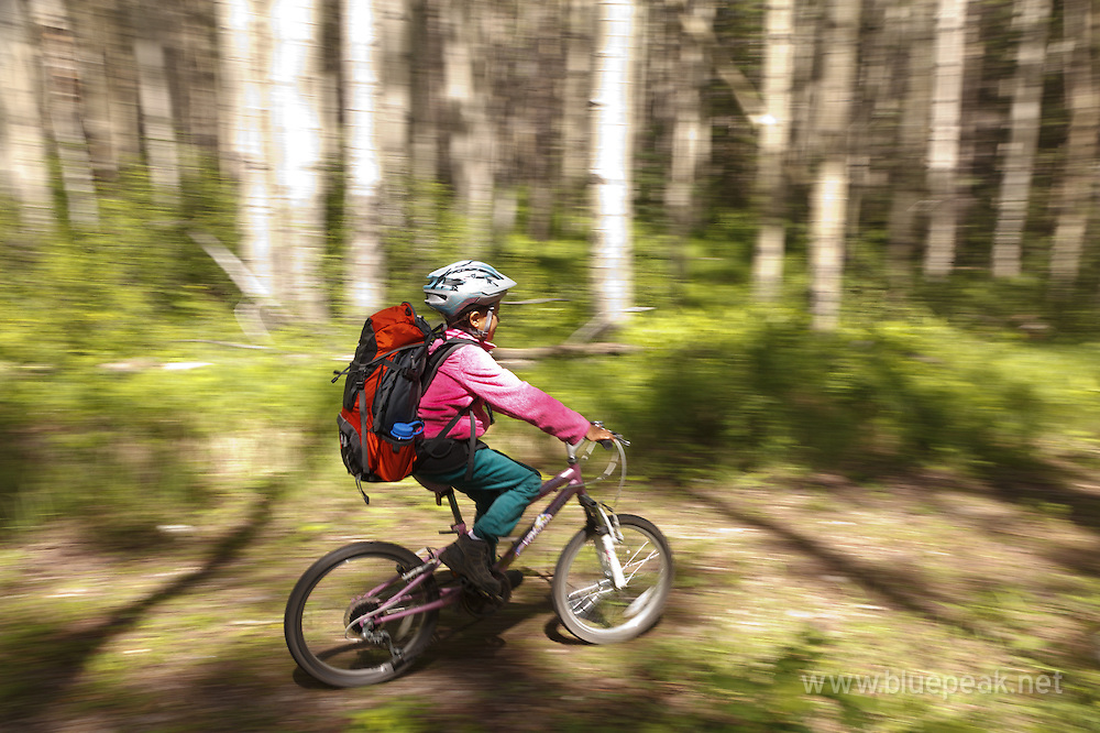 Girl cycling on the North Boundary Trail in Jasper National Park, Canada