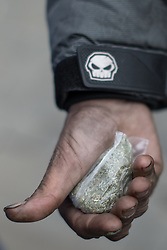 © Licensed to London News Pictures . 06/04/2017 . Manchester , UK . A homeless man holds out his hand to show a bag of spice he says he has bought for £20 , which he describes as a single day's supply for himself . An epidemic of abuse of the drug spice by some of Manchester's homeless population , in plain sight , is causing users to experience psychosis and a zombie-like state and is daily being witnessed in the Piccadilly Gardens area of Manchester , drawing large resource from paramedic services in the city centre . Photo credit : Joel Goodman/LNP