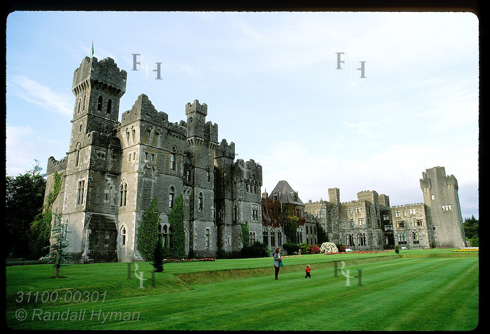 Mother and toddler play on vast green lawn with Ashford Castle hotel looming behind; Cong. Ireland