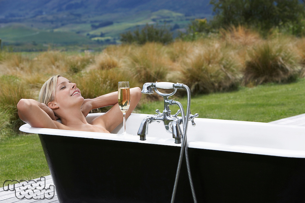 Woman taking bath with champagne on porch in countryside