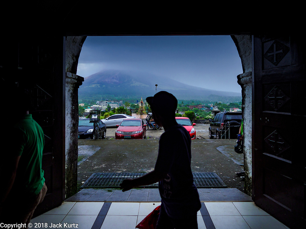 21 JANUARY 2018 - LEGAZPI, ALBAY, PHILIPPINES: A man walks past a door at Our Lady of the Gate Parish (Parroquia Nuestra Señora de la Porteria) with the cloud shrouded Mayon volcano in the background. The Mayon volcano continued to release smoke and ash Sunday morning. Mayon is the most active volcano in the Philippines. More than 30,000 people have been evacuated from communities on the near the Mayon volcano in Albay province in the Philippines. Most of the evacuees are staying at schools in communities outside of the evacuation zone.    PHOTO BY JACK KURTZ