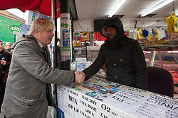 © licensed to London News Pictures. London, UK 25/03/2013.The Mayor of London Boris Johnson talking to shop owners as he joins members of the Dalston Safer Neighbourhood Team on their local beat to launch the Mayor's Police and Crime Plan on Dalston Kingsland High Street in London. Photo credit: Tolga Akmen/LNP