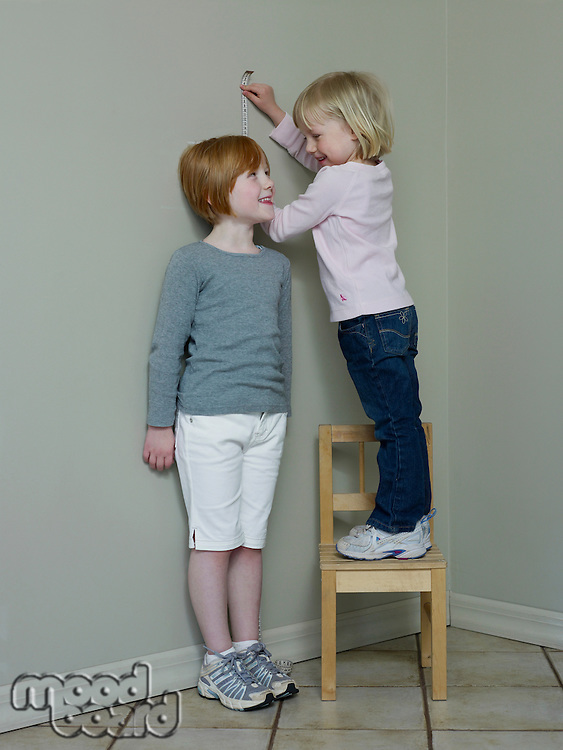 4-5 year old girl measures 7-8 year old against wall