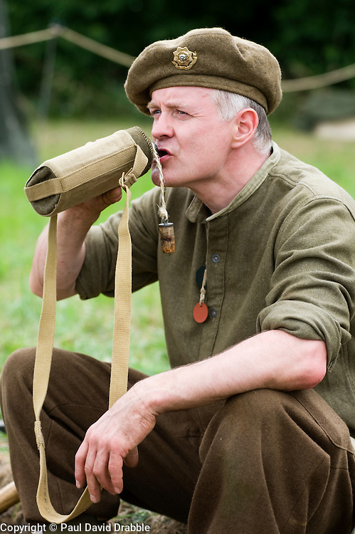 A re-enactor from the Northern World War Two Association Living History group portrays a member of the British 5th Battalion, East Yorkshires, 50th Division drinks from his water bottle. SPAM 1940's Weekend Heckmonwyke near Wakefield 10 July 2010 .Images © Paul David Drabble..