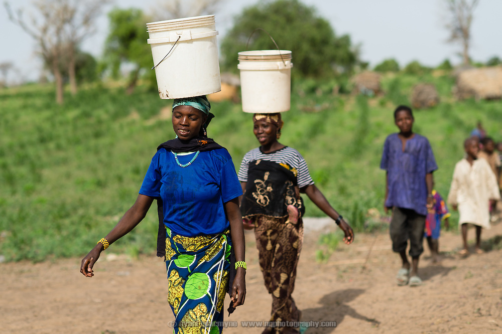 """Women carrying water home from a WaterAid pump in the village of Kanwa-Maraki in the Zinder Region of Niger on 25 July 2013. When asked about the pump as compared to the villages previous water source she said, """"The water tastes good, and there is no risk of sickness when you drink it."""" She is accompanied by her daughter, Haouaou Maharadou, 3."""