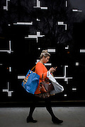 Lady consumer and shopping bags with a background of a geometric-designed wall in central London