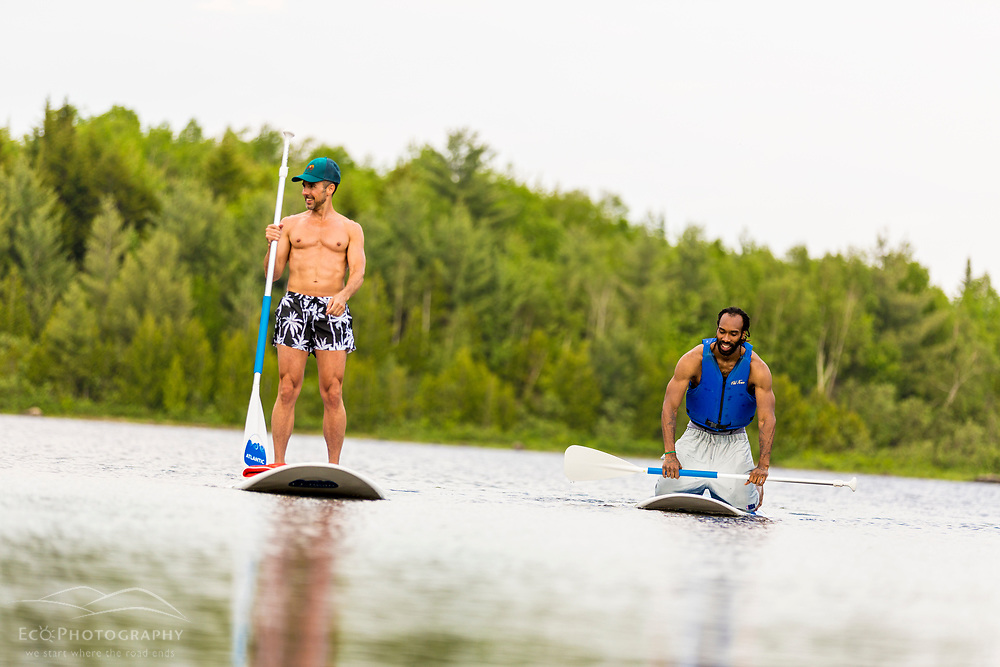 Two men paddleboarding on Second Roach Pond near the Appalachian Mountain Club's Medawisla Lodge in the Maine Woods near Greenville.