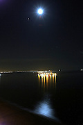 An oil pumping island reflects off the water at night with a full moon in the night sky and Mars to the lower left of the moon over Long Beach Harbor in Long Beach, California on August 12, 2003. ©Paul Anthony Spinelli