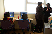 Second grade students work in the computer lab as D.C. Public Schools Chancellor Kaya Henderson talks to the computer lab teacher, Geraldine Chambers, at Truesdell Education Campus on Friday, Nov. 16, 2012 in Washington, D.C. Henderson recently announced that she plans to close 20 under-enrolled schools across the district. CREDIT: Lexey Swall for The Wall Street Journal