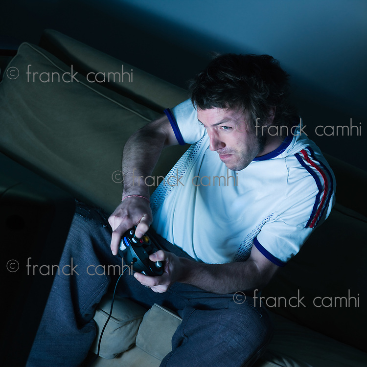 pictures in a living room a funny and expresive man sitting on a couch   playing video game