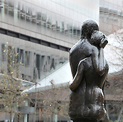 The Young Lovers sculpture, City of London, England. This life-size bronze sculpture is by Georg Ehrlich, 1897-1966, Austrian sculptor, and is situated in Festival Gardens, Cannon St, in the City of London. It was erected in 1973. In the background is One New Change, 2010, by Jean Nouvel, a retail and office development. Picture by Manuel Cohen
