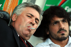 Milan manager Carlo Ancelotti enjoys a cigarette on the bench during the Serie A match between Udinese and Milan.