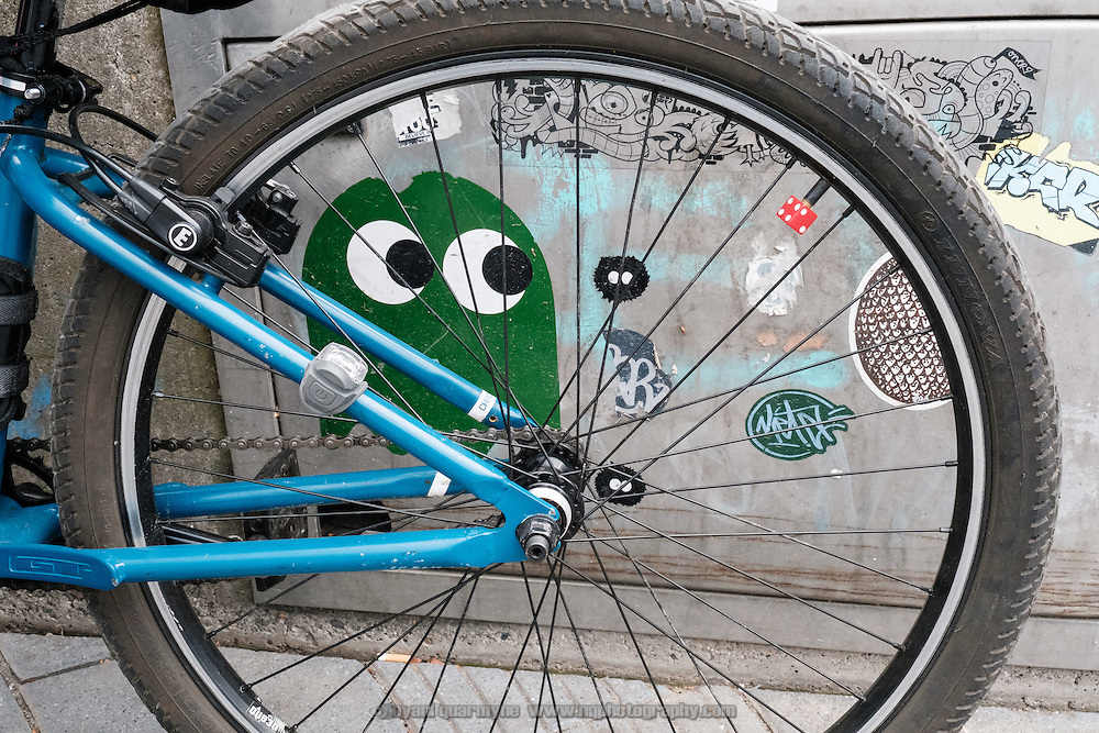 A PacMan ghost sticker by urban artist Pdot peeks out from behind a bicycle wheel in Düsseldorf, Germany on 26 July 2016.