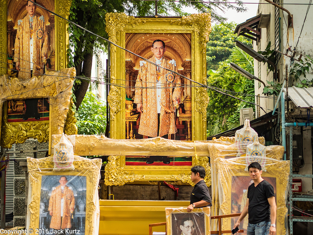 18 OCTOBER 2016 - BANGKOK, THAILAND: Men, one carrying a portrait of the King, walk past large paintings of Bhumibol Adulyadej, the late King of Thailand. King Bhumibol Adulyadej died Oct. 13, 2016. He was 88. His death came after a period of failing health. Bhumibol Adulyadej was born in Cambridge, MA, on 5 December 1927. He was the ninth monarch of Thailand from the Chakri Dynasty and is also known as Rama IX. He became King on June 9, 1946 and served as King of Thailand for 70 years, 126 days. He was, at the time of his death, the world's longest-serving head of state and the longest-reigning monarch in Thai history.     PHOTO BY JACK KURTZ