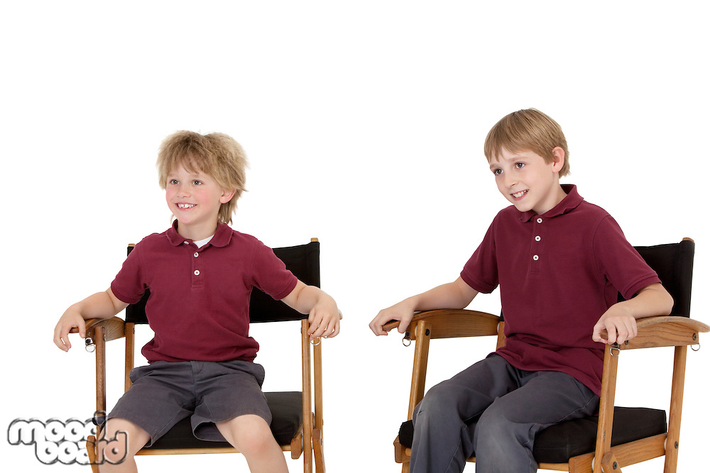 Two happy school kids sitting on director's chair over white background
