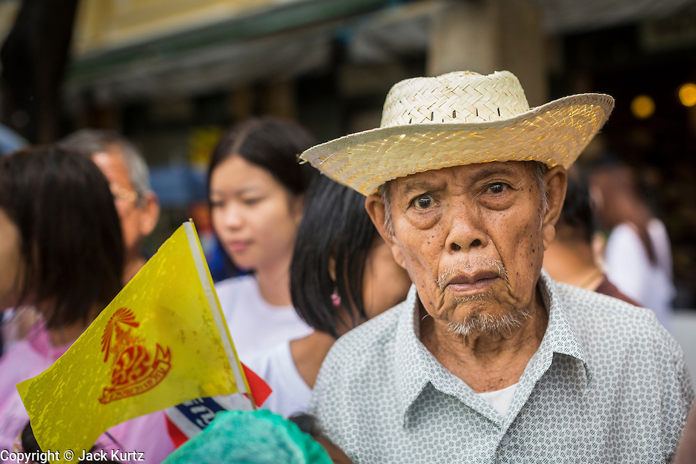 "05 MAY 2013 - BANGKOK, THAILAND:   A Thai man waits to see Bhumibol Adulyadej, the King of Thailand, Sunday. The King and Queen, who are both hospitalized and in poor health, did not attend Sunday's event. May 5 marks the 63rd anniversary of the Coronation of His Majesty King Bhumibol Adulyadej. The day is celebrated as a national holiday; since this year it falls on a Sunday, it will be observed on Monday May 6, and as such all government offices and commercial banks will close for the day. HM King Bhumibol Adulyadej is the longest reigning monarch in the world. Each year on the 5th of May, the Kingdom of Thailand commemorates the day when, in 1950, the Coronation Ceremony was held for His Majesty King Bhumibol Adulyadej, the 9th in the Chakri Dynasty (Rama IX). On the 5th of May, His Majesty conducts a merit making ceremony, presenting offerings to Buddhist monks, and leads a ""Wien Thien"" ceremony, walking three times around sacred grounds at the Temple of the Emerald Buddha.    PHOTO BY JACK KURTZ"