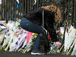 © Licensed to London News Pictures. 28/01/2018. London, UK. A woman places flowers at the scene where three teenage pedestrians were killed near a bus stop in Hayes, West London when a black Audi collided with them. Named locally as Harry Rice, Josh Kennedy and George Wilkinson, the three teenagers were hit on Friday night  close to the M4 Junction 4. A 28-year-old man has been arrested and a police are currently looking for a  second man believed to have been in the Audi.. Photo credit: Ben Cawthra/LNP