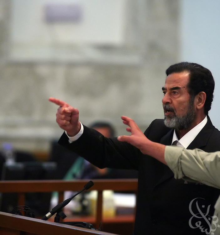 A court deputy reaches for the former Iraqi leader Saddam Hussein as he gestures defiantly after being sentenced to death during his trial in the heavily fortified Green Zone November 5, 2006. Hussein was executed by the Iraqi government in December 2006. (Photo by Scott Nelson/World Picture Network)