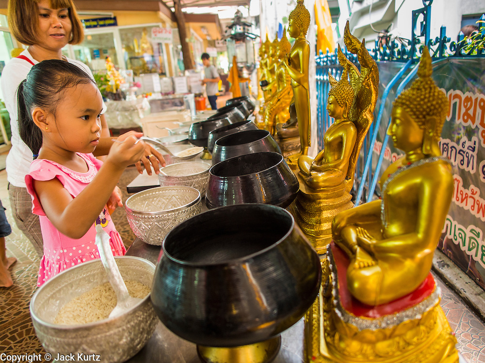 "10 APRIL 2014 - BANGKOK, THAILAND: A girl makes merit at Wat That Thong in Bangkok before Songkran. Songkran, also called the ""Water Festival"" is the traditional Thai New Year. It was celebrated as the New Year until 1940, when Thailand made January 1 the official start of the New Year. Songkran is now a three day holiday starting on April 13. Many people go to temples to make merit in the days leading up to Songkran. They bathe Buddha statues to bring themselves good luck in the coming year. The holiday is best known for water fights and throwing water at strangers. Thais and foreigners go out with giant squirt guns or buckets of water and throw the water at strangers.    PHOTO BY JACK KURTZ"