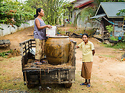20 JANUARY 2016 - SI LIAM, BURI RAM, THAILAND:  Neighbors talk about the drought in Thailand. The woman in the tractor (left) goes out looking for water and then sells what she doesn't use. The drought gripping Thailand was not broken during the rainy season. Because of the Pacific El Nino weather pattern, the rainy season was lighter than usual and many communities in Thailand, especially in northeastern and central Thailand, are still in drought like conditions. Some communities, like Si Liam, in Buri Ram, are running out of water for domestic consumption and residents are traveling miles every day to get water or they buy to from water trucks that occasionally come to the community. The Thai government has told farmers that can't plant a second rice crop (Thai farmers usually get two rice crops a year from their paddies). The government is also considering diverting water from the Mekong and Salaween Rivers, on Thailand's borders to meet domestic needs but Thailand's downstream neighbors object to that because it could leave them short of water.       PHOTO BY JACK KURTZ