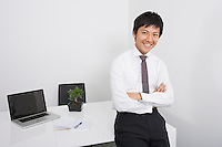 Portrait of happy Asian businessman with arms crossed leaning on office desk