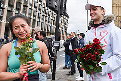 "© Licensed to London News Pictures. 08/03/2017. London, UK. Tourists Elizabeth Wang from San Francisco receives roses.  A flashmob takes place in Parliament Square as part of International Women's Day.  Apparently backed by the Russian government, a giant balloon is unsuccessfully inflated bearing the text ""From Russia With Love"" and ""#makehersmile"" with organisers handing out roses to unsuspecting female passers by. Photo credit : Stephen Chung/LNP"