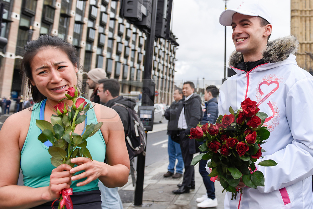"""© Licensed to London News Pictures. 08/03/2017. London, UK. Tourists Elizabeth Wang from San Francisco receives roses.  A flashmob takes place in Parliament Square as part of International Women's Day.  Apparently backed by the Russian government, a giant balloon is unsuccessfully inflated bearing the text """"From Russia With Love"""" and """"#makehersmile"""" with organisers handing out roses to unsuspecting female passers by. Photo credit : Stephen Chung/LNP"""