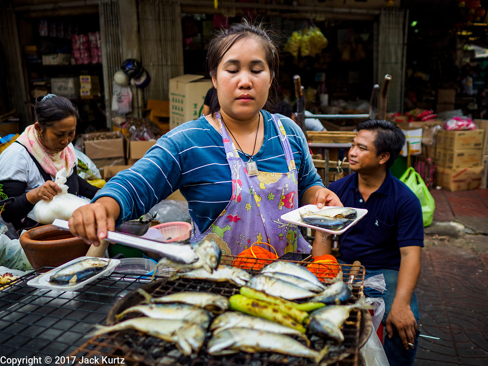 "18 MAY 2017 - BANGKOK, THAILAND: A woman grills fish on a street in Bangkok's Chinatown. City officials in Bangkok have taken steps to rein in street food vendors. The steps were originally reported as a ""ban"" on street food, but after an uproar in local and international news outlets, city officials said street food vendors wouldn't be banned but would be regulated, undergo health inspections and be restricted to certain hours on major streets. On Yaowarat Road, in the heart of Bangkok's touristy Chinatown, the city has closed some traffic lanes to facilitate the vendors. But in other parts of the city, the vendors have been moved off of major streets and sidewalks.      PHOTO BY JACK KURTZ"
