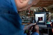 """Avigliano (PZ), 04-10-2010 ITALY - Vito Aquila, artigiano di Balestre. Il coltello di Avigliano, comunemente conosciuto come """"balestra"""", impreziosito con decorazioni in argento e ottone che le conferivano un certo valore non solo artistico,ha identificato per tutto l'Ottocento e parte del Novecento il carattere fiero e risoluto del popolo aviglianese, come attestato in una lunga casistica di riscontri documentari. La """"balestra"""" è un'arma a tutti gli effetti, ed è già considerata -nell'ambito delle manifatture di ferro - oggetto di pregio. Per l'approvvigionamento dell'argento e dell'ottone destinati alla decorazione del manico del coltello gli armieri si rivolgevano agli orefici o agli ottonari. La """"balestra"""" era un'arma del popolo, pronta ad essere impiegata, a seconda delle circostanze, per la difesa o l'offesa tanto dagli uomini quanto dalle donne. Queste, la ricevevano come regalo di fidanzamento dal rispettivo promesso sposo per meglio difendere il proprio onore, perpetrando un'usanza molto sentita almeno fino ai primi decenni del '900..Nella Foto: La lama viene passata nel forno a temperature altissime."""