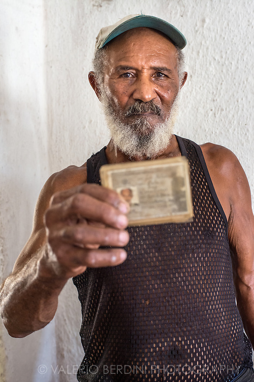 Luiz Antonio Bello Diez old member of Cuban revolutionary Army (ejercito rebelde), who fought key battles in the late 50s in support of the socialist revolution alongside Camilo Cienfuegos, shows his army ID card. Caibarien. Cuba, 2015.