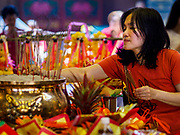 15 FEBRUARY 2018 - BANGKOK, THAILAND:  A woman wearing red for Lunar New Year lights incense and prays during Lunar New Year observances at Wat Mangkon Kamalawat in Bangkok's Chinatown. Wat Mangkon Kamalawat is the largest Chinese temple in Chinatown. Lunar New Year, also called Tet or Chinese New Year, is 16 February this year. The coming year will be the Year of the Dog. Thailand has a large Chinese community and Lunar New Year is widely celebrated in Thailand, especially in Bangkok and large cities with significant Chinese communities.    PHOTO BY JACK KURTZ