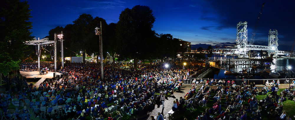 An overview of the Prescott Park Arts Festival scene in Portsmouth, NH,  during a concert by Judy Collins in August, 2013. The new Memorial Bridge was lit up brightly (at right) for final inspection before it opened to traffic for the first time the next day.